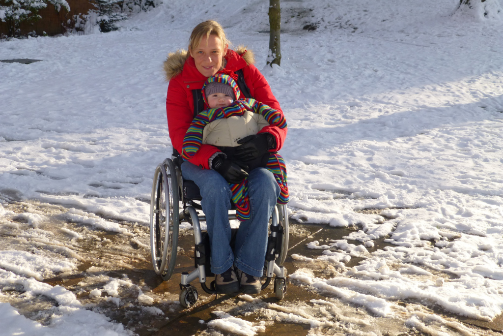 Clair, a spinal cord injured mum, holding her baby on her lap in a snowy field