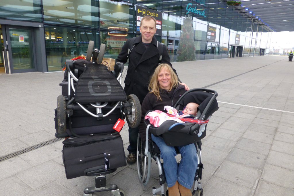 Clair in an airport with her luggage, her partner, and her baby daughter on her lap in a car seat