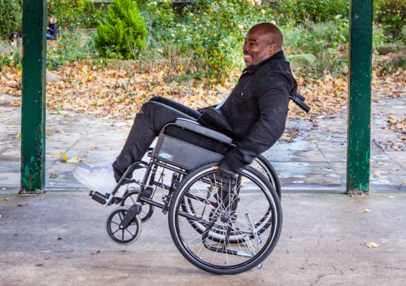 "a wheelchair user practicing a back wheel balance. ""What Next?"" can help you live well after spinal cord injury."