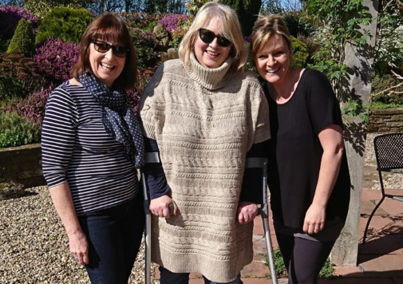Caroline stands using her crutches with some friends