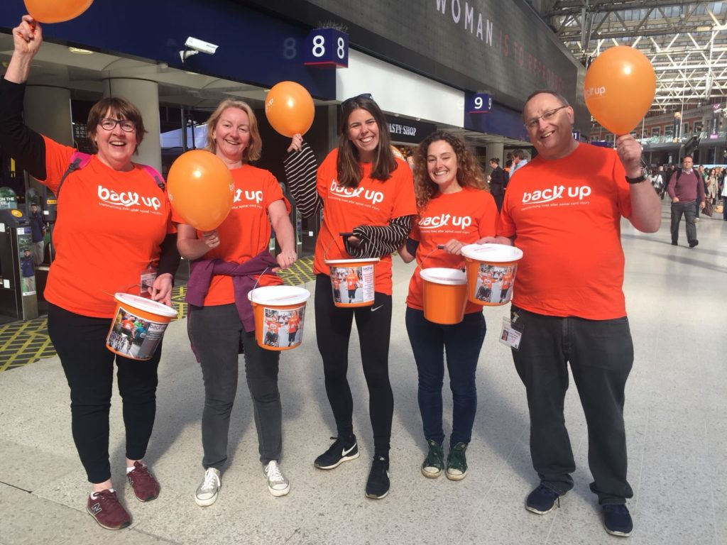 five Back Up volunteers holding balloons at London Waterloo bucket collection