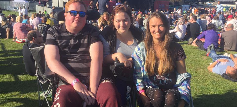 A group of three friends at an outdoor festival. Two of them are wheelchair users.