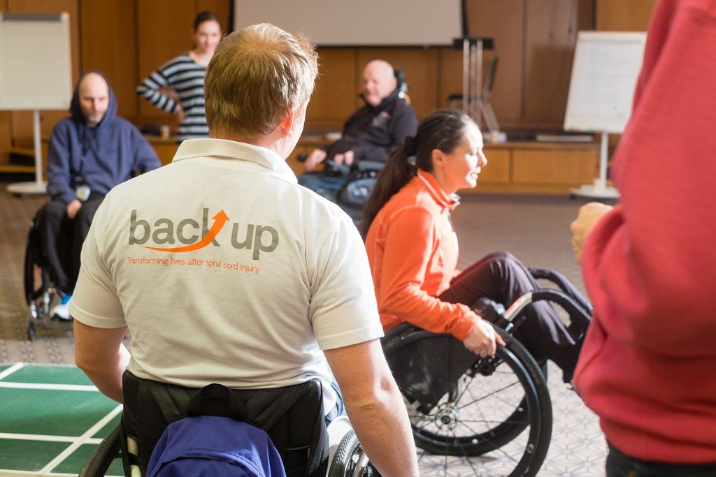 Back Up wheelchair skills trainer overlooking a training session