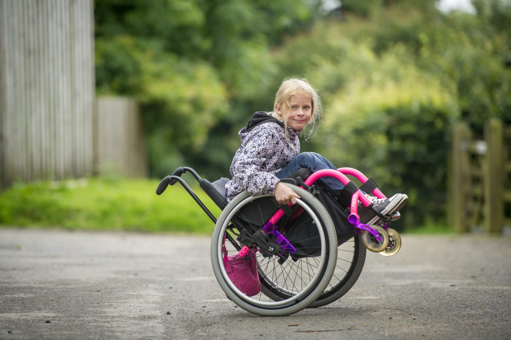 Young wheelchair user doing a back wheel balance