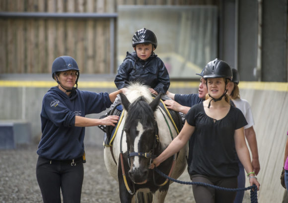 Young wheelchair user riding a horse with volunteers near