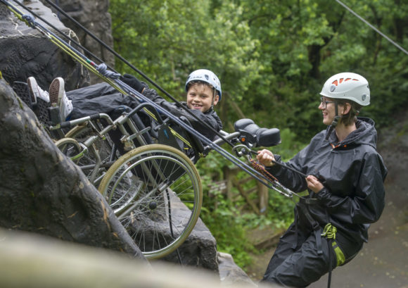 Young wheelchair user and volunteer abseiling