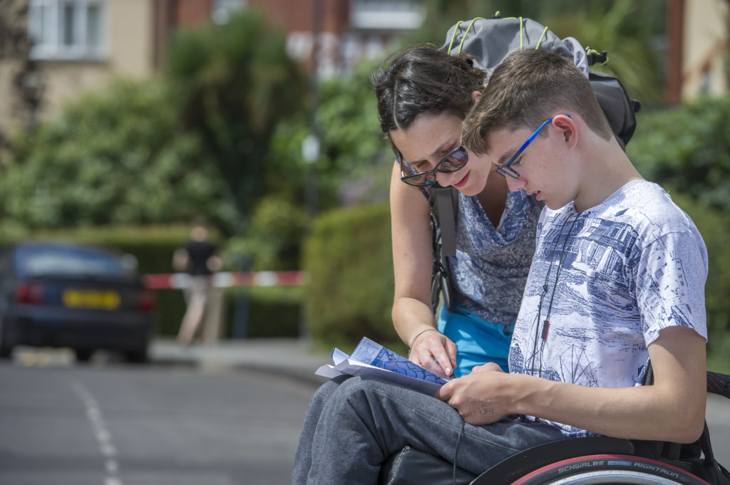 A volunteer and young wheelchair user reading a treasure hunt map on a course