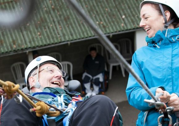 Wheelchair user and volunteer abseiling on a course