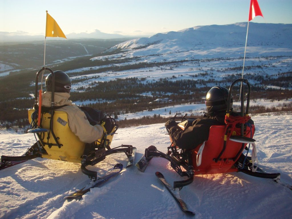 Two wheelchair users in ski karts overlooking a mountain