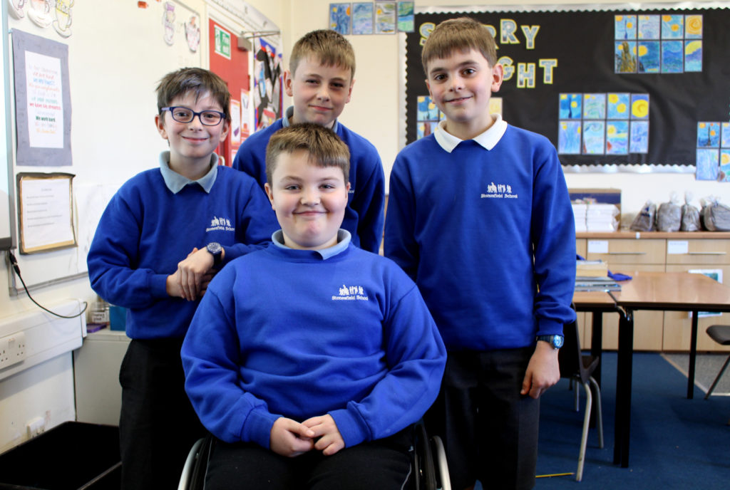 Young wheelchair user and friends at school