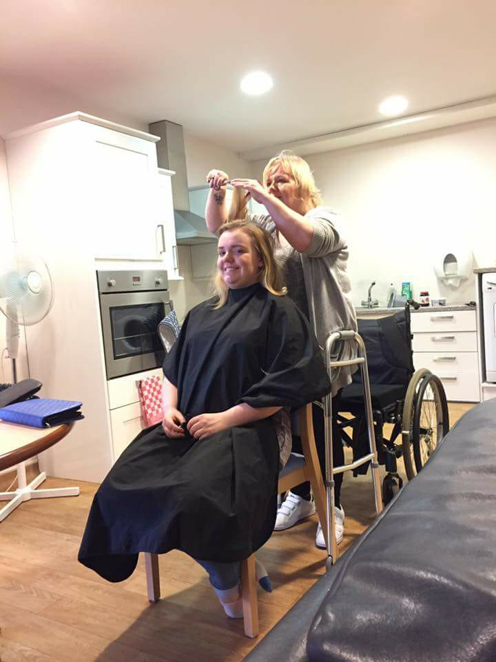 Fiona stands while cutting someone's hair